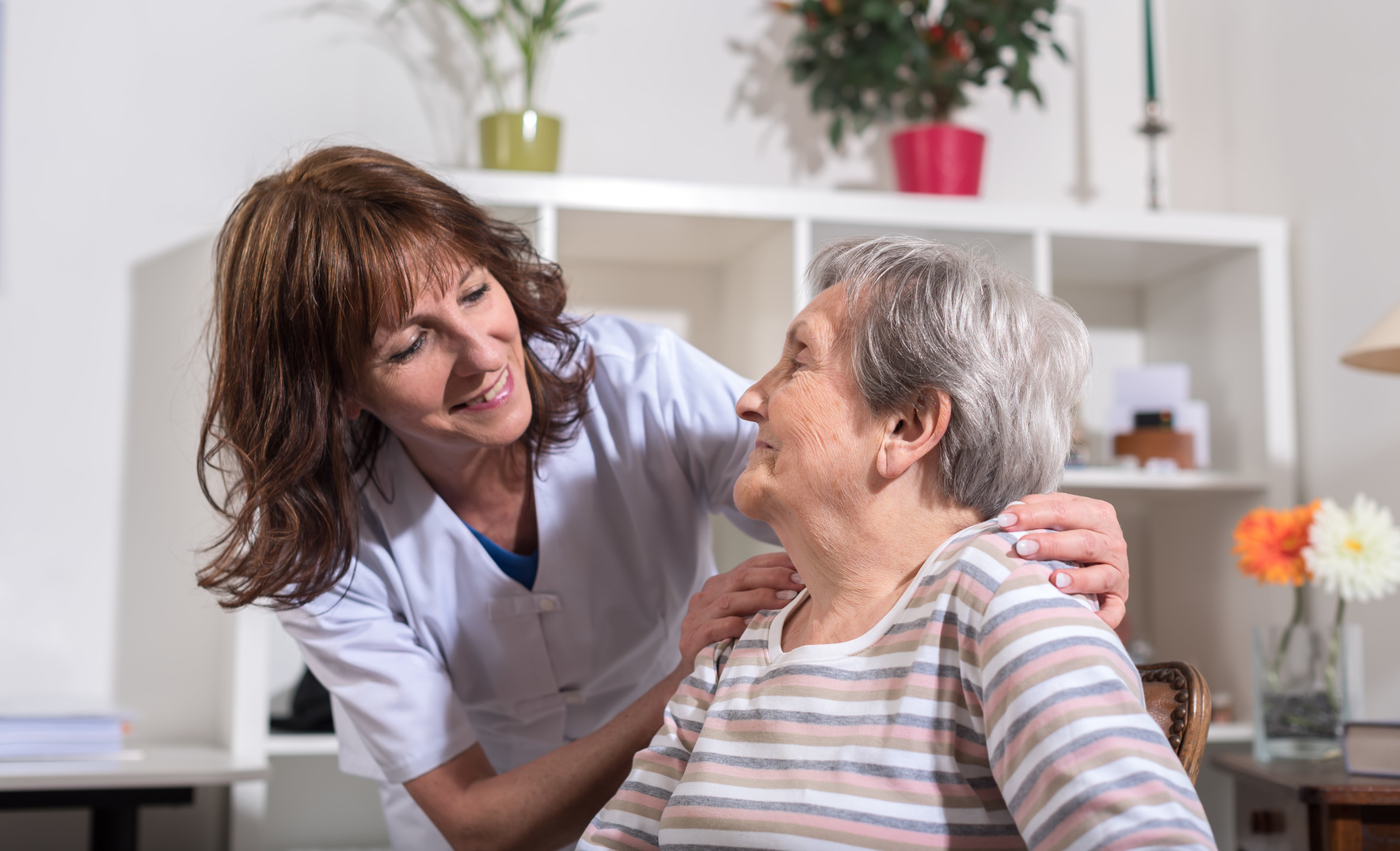 Nurse with her hands on the shoulder of a senior woman